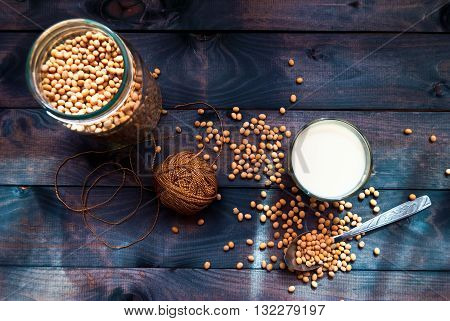 Glass of soy milk and dried soy beans in the spoon and jar on wooden background. Top view