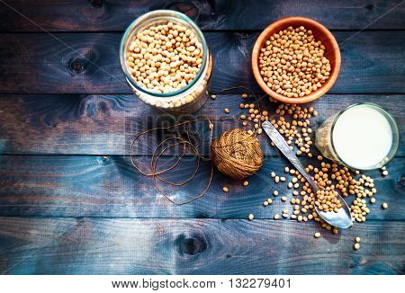 Glass of soy milk and dried soy beans in the spoon bowl and jar. Image with space for text