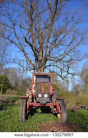 old used retro agriculture tractor in farm and big oak