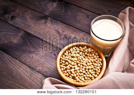 Glass of soy milk and full bowl of soy beans on wooden background. Rural style. Copy space