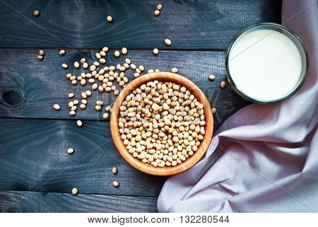 Glass of soy milk and bowl of soy beans on blue wooden background with light pink kitchen towel