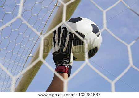 goalkeeper's hands reaching for the foot ball