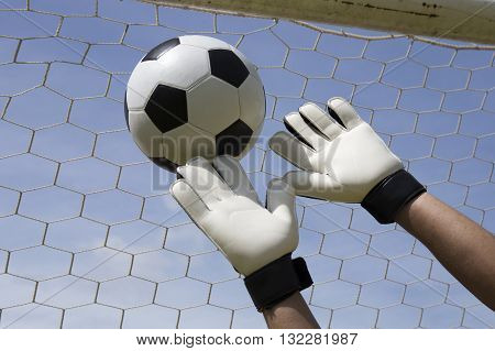 A goalkeeper's reaching for the foot ball