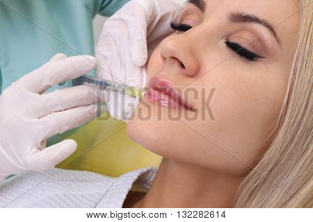 Beautiful girl on rejuvenation procedure in beauty clinic filler injection. Injection in her lips.