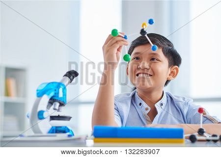 Happy schoolboy looking at molecular model in his hands