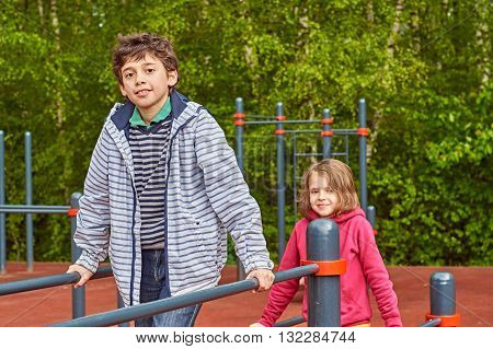 Handsome boy and girl posing on uneven bars outdoors