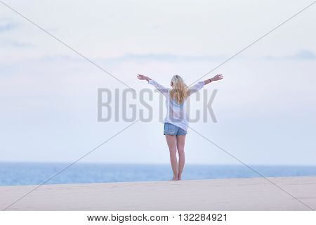 Relaxed woman enjoying freedom feeling happy at beach in the morning. Serene relaxing woman in pure happiness and elated enjoyment with arms raised outstretched up.