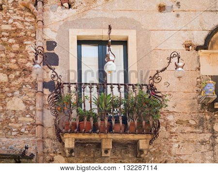Historic house with balcony and plants in Italy