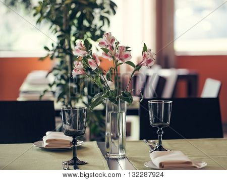 Pink alstromeria with green leaves in vase on table near empty glasses in cafe interior