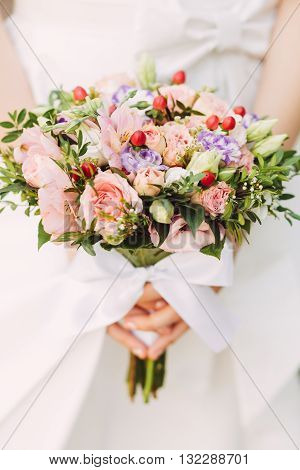 Female hands holding beautiful bridal bouquet with roses and red berries in summer