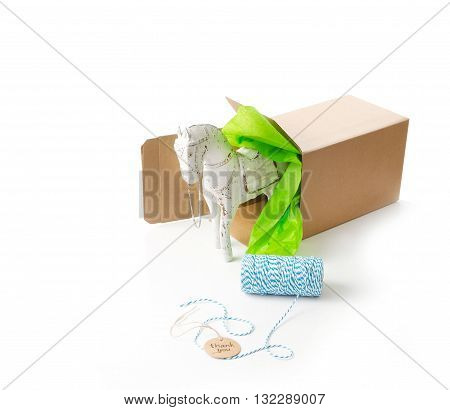 gift wrapping supplies with toy wooden horse in craft gift box with tissue paper.
