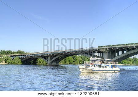 KIEV UKRAINE - May 10.2012: Metro bridge across the Dnieper River and floating excursion boat