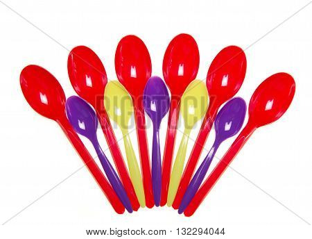 Multi-colored plastic spoons isolated on white background.