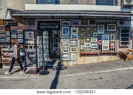 Mostar Bosnia and Herzegovina - August 25 2015. Woman walks in front of souvenir shop with local paintings and postcards in Mostar