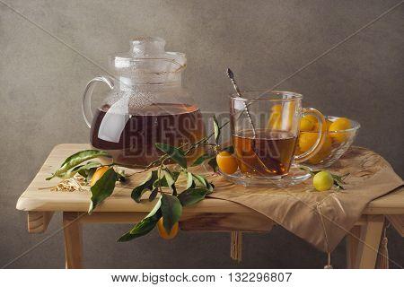 Tea with fresh kumquat lemons on wooden table