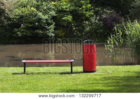 Red public bench and garbage can in grass near water