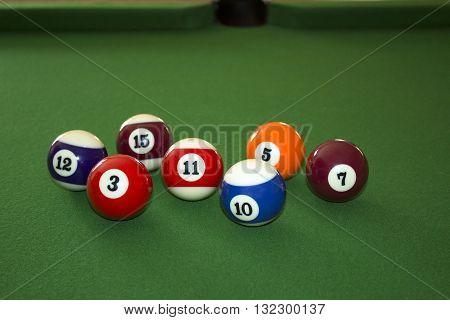 A photograph of seven pool balls / billiard balls (full and semi-focus)