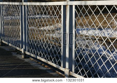 The road is fenced by a metal fence.