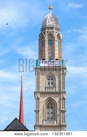 Zurich, Switzerland - 25 May, 2016: tower of the Grossmunster cathedral with a banner which is a part of the promotion devoted to the World Refugee Day on the 20th of June arranged by aid organization of Evangelic Churches of Switzerland.