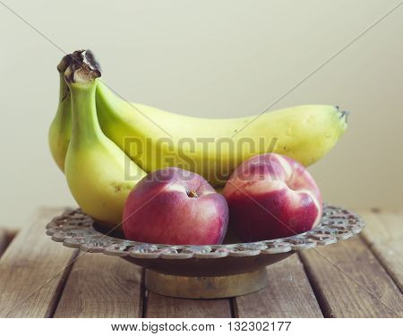 Fruits in vintage bowl on wooden table
