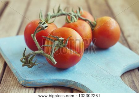 Tomatoes on cutting board on wooden table