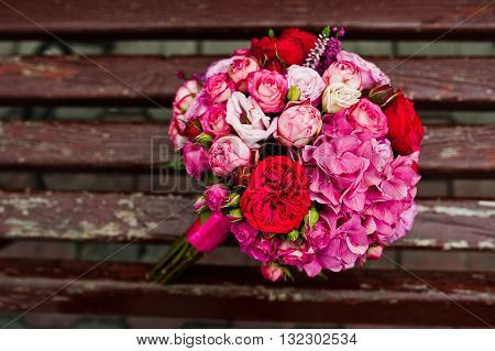 Wedding bouquet of rose and peony david austin background wooden bench