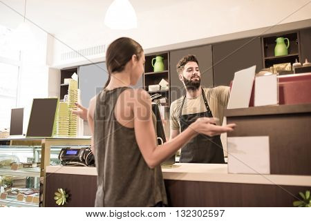 Two beautiful young woman buying coffee in a coffee shop from a barista guy