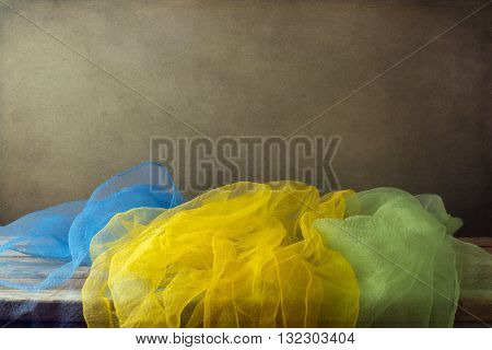 Background with colorful gauze scarf and wooden deck table