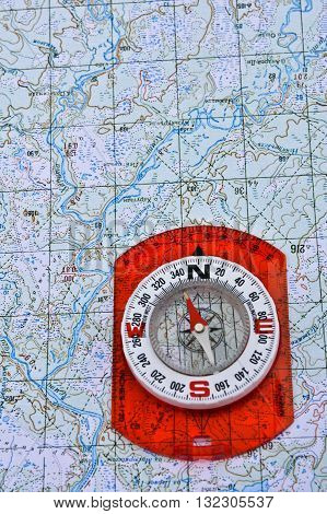 Map and compass. Magnetic compass is located on a topographic map.
