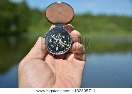 Man's hand holding compass on the contrary refocusing summer landscape.