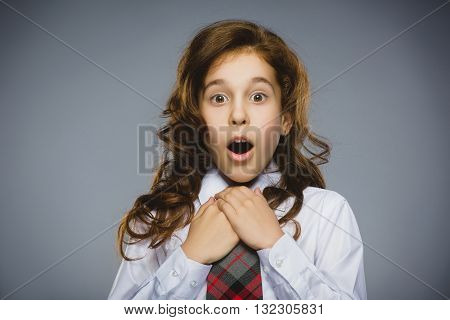 Portrait of happy girl going surprise on gray background.