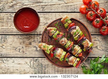 Barbecued turkey or chicken meat shish kebab skewers with ketchup sauce, chopped parsley and tomatoes on rustic wooden table background. Traditional barbecue grill food