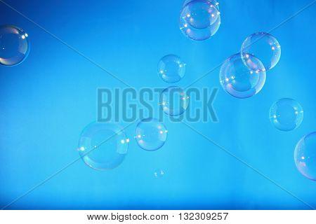 Rainbow soap bubbles on a blue backgrounds
