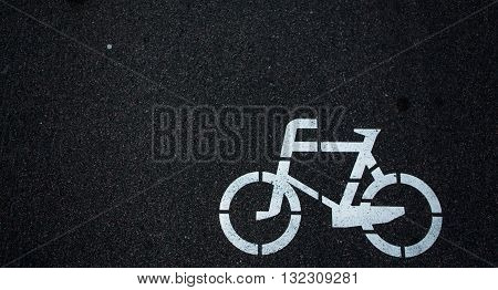 Bicycle road sign of white colour on road. Bicycle sign path on road, bikes' lane on outskirts or urban area.