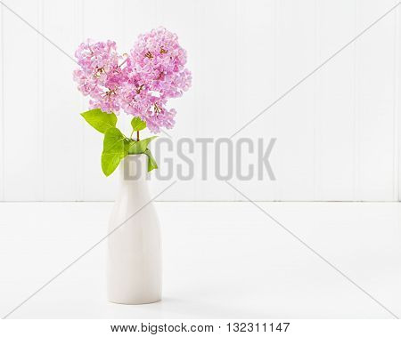 Beautiful purple lilacs in a vase with abundant copy space.