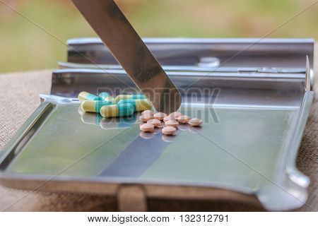 Healthcare and medical concept. Heap of different pills tablets pouring in the stainless plate