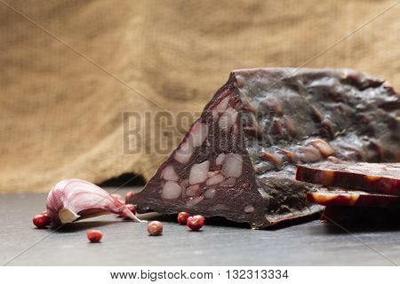 jerked sausage and spices on a dark background
