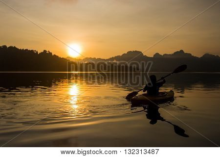 Silhouette man kayaking in lake at sunrise