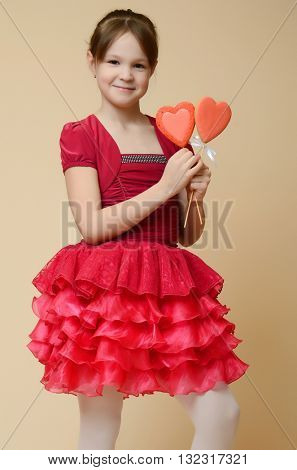 Emotional caucasian little girl holding heart shape biscuits on Valentine Day
