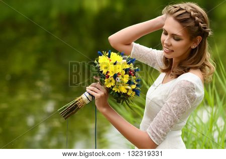 Beautiful natural young blonde smiling  woman on field keep in hand yellow flowers