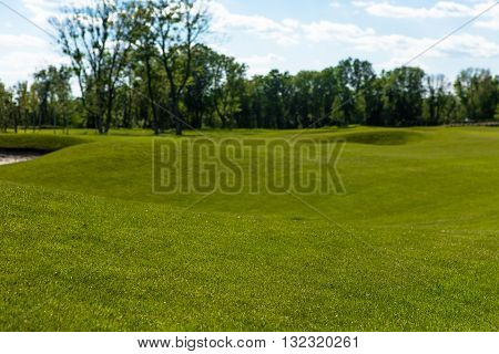 Green golf course and blue sky. Nice nature and environment with blue sky and white clouds. Sand bunkers at beautiful golf course at sunset, sunrise time.