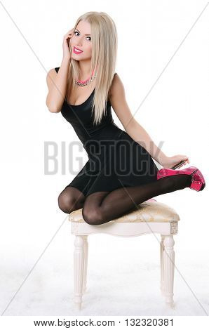 Beautiful sensual woman sits on a chair
