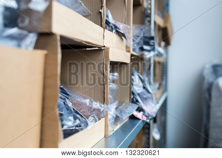 Close-up of cardboard boxes on rack in traditional indoors warehouse.