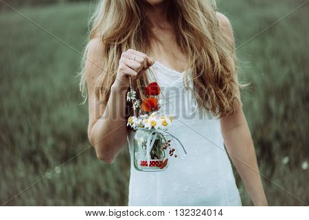 Close up of beautiful girl with flower in the summer park. Woman picking flowers.