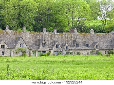 Row of traditional English cottages in charming Cotswolds village Bibury with meadow in front and trees in the back garden
