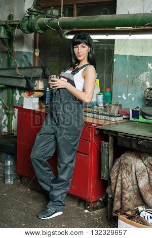 a young woman as a mechanic in a garage. rare professions for women. girl mechanik have a coffe break and resting.