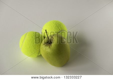 Golden yellow aple in front of two tennis balls on white background