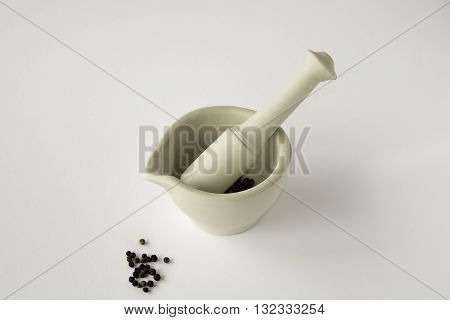 Looking down on ceramic mortar and pestle with blck peppercorns on white background