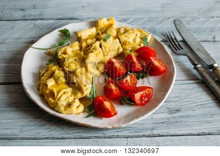 Breakfast on a ceramic plate omelet with herbs and cherry tomatoes scrambled eggs with tomatoes