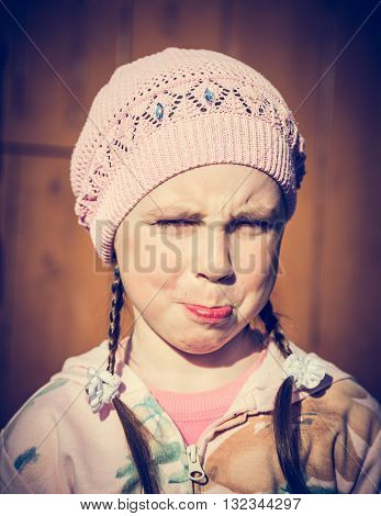 Close-up portrait of sad little girl with pursed lips. Photos in retro style.